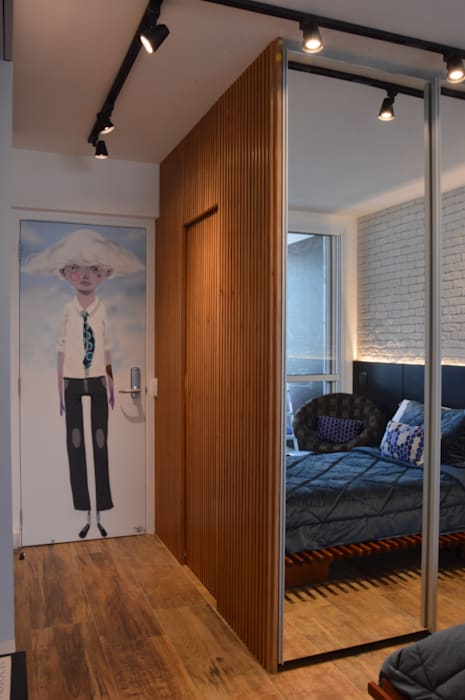 Hall com porta embutida no painel de madeira ripada: Corredores e halls de entrada  por Studio Elã