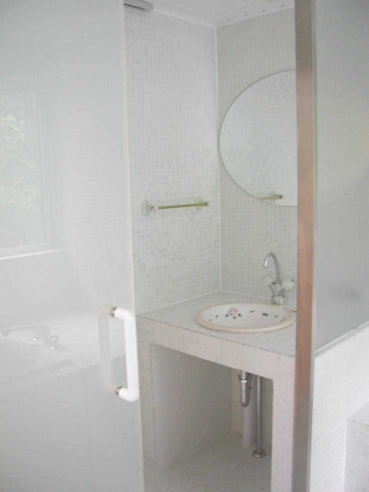 サンルームのある別荘: フナキサチコケンチクセッケイジムショが手掛けた浴室です。,