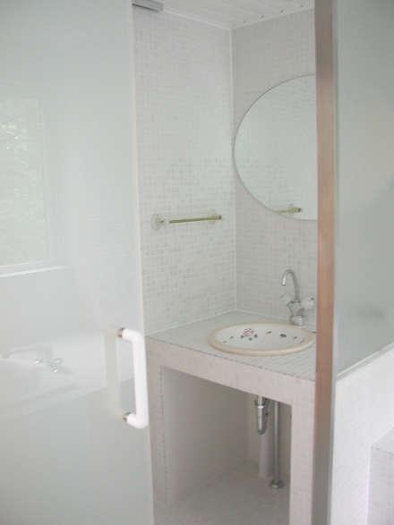 サンルームのある別荘: フナキサチコケンチクセッケイジムショが手掛けた浴室です。
