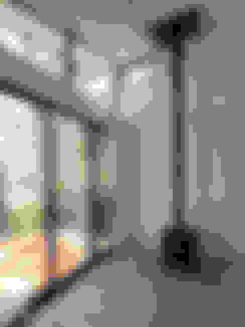 リビングルームの一角に設置した小さな薪ストーブ: 大庭建築設計事務所が手掛けたリビングです。