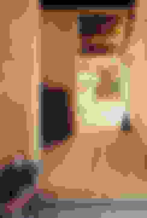 玄関から居間を望む: 小栗建築設計室が手掛けた壁です。