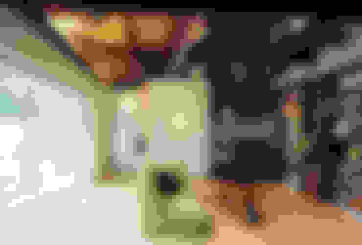居間と庭に続くデッキ: 小栗建築設計室が手掛けたリビングです。