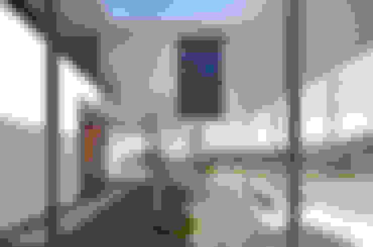 中庭にもなるピロティー: 松本匡弘建築設計事務所が手掛けたテラス・ベランダです。