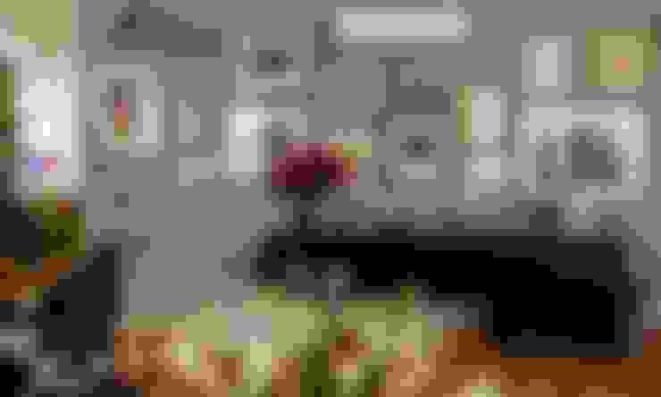 detalhe da parede com quadros: Salas de estar  por acr arquitetura