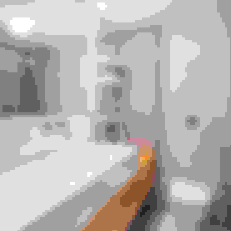 Reforma de apartamento - Simmetria Arquitetura: Banheiros  por Joana França