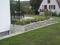 Kleines Pflanzbeet an der Terrasse: an der Schmalseite L-Steine aus Beton, längs wieder die gebrauchten Granit-Bordsteine.:   von KAISER + KAISER - Visionen für Freiräume GbR