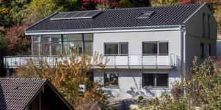 Schwarz engobierte Ziegel, eine graue Putzfassade und große dunkelgraue Fenster sprechen die Architektursprache der späten 10er Jahre: moderne Häuser von KitzlingerHaus GmbH & Co. KG