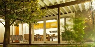 中庭からリビングダイニングを見る: FrameWork設計事務所が手掛けた庭です。