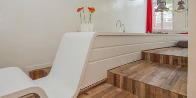 Strak wit Corian en oud grof hergebruikt hout: moderne Keuken door CUBE architecten