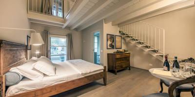 Le 4 camere accolgono gli ospiti nell'atmosfera primi '900: Hotel in stile  di STUDIO PAOLA FAVRETTO SAGL - INTERIOR DESIGNER