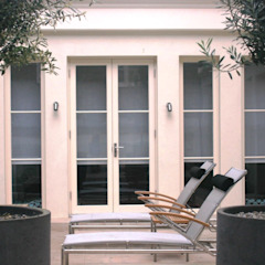 Loungers and Olive trees in the lower atrium by Rae Wilkinson Rae Wilkinson Design Ltd Minimalist style garden