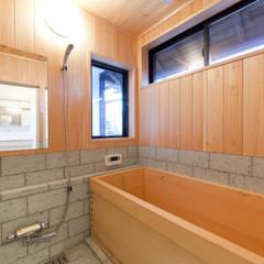 伝統のしつらえと、モダンライフの融合: 吉田建築計画事務所が手掛けた浴室です。