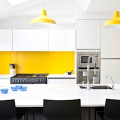 White, black, stainless steel and a vibrant splash of yellow.:  Kitchen by Pyram