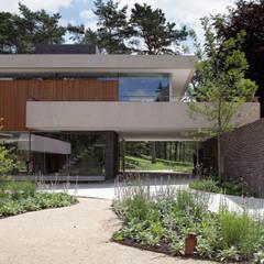 De onderdoorgang verbindt de gecultiveerde voorhof met het bos achter de duinvilla.:  Huizen door HILBERINKBOSCH architecten