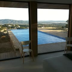 Zicht op het zwembad vanuit de woonkamer:  Woonkamer door TenBrasWestinga ARCHITECTUUR / INTERIEUR en STEDENBOUW