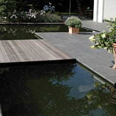 Holzsteg aus Bangkirai in Verbindung mit Wasserfläche und Basalt Natursteinplatten: moderner Garten von Grünplanungsbüro Jörg baumann