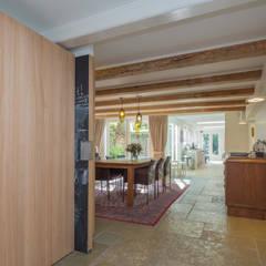 eetkamer en keuken aan de tuin: eclectische Eetkamer door CUBE architecten