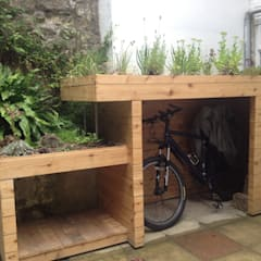 Bike and log store with green roof:  Garden by Organic Roofs