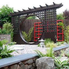 The moon gate with wooden art behind:  Garden by Lush Garden Design