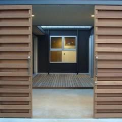中庭を挟んだ二世帯住宅: 三浦尚人建築設計工房が手掛けたガレージドアです。