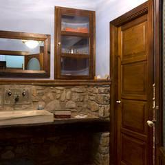 Restauración de masia guardando la esencia de los años: Baños de estilo  de Puigdesens fusteria interiorisme