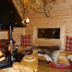 The interior of a 10m² cabin, fire going lovely cushions and reindeer skins on the benches. :  Garden by Arctic Cabins