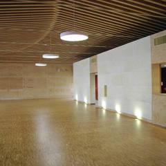 la grande salle: le mur en pierre massives et la charpente dense: Lieux d'événements de style  par LCD'O Le compas dans l'oeil architectes
