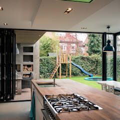 Aanbouw en renovatie van 2-onder-1-kapper met ruime woonkeuken met kookeiland, gietvloer en luxe aluminium vouwschuifpui:  Keuken door Joep van Os Architectenbureau
