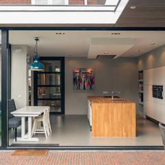 Aanbouw en renovatie van 2-onder-1-kapper met ruime woonkeuken met kookeiland, gietvloer en luxe aluminium vouwschuifpui:  Terras door Joep van Os Architectenbureau, Modern