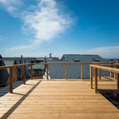 ルーフバルコニーからは葉山の海眺望: エンジョイワークス一級建築士事務所が手掛けたベランダです。