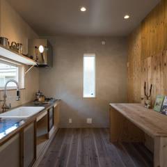 ステンレスと古い建具、多様な木の表情が混ざり合うキッチン: エンジョイワークス一級建築士事務所が手掛けたキッチンです。