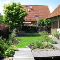Gerade Stege und Terrassen bilden einen Kontrast zu den geschwungenene Rasen- und Pflanzflächen:  Garten von Tina Brodkorb Landschaftsarchitektur