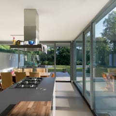 De woonkeuken met overdekt terras en volledig zicht op tuin:  Keuken door Architect2GO