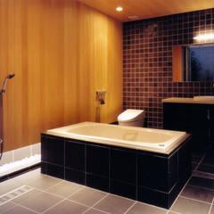 コンクリート打ち放しのモダン和風住宅: 豊田空間デザイン室 一級建築士事務所が手掛けた浴室です。