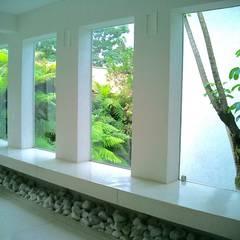 Bancada do ambiente social rodeada por jardim tropical : Janelas   por Kika Prata Arquitetura e Interiores.