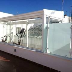 Gimnasio de Cristal Lumon y techo movible de cristal, Terraza con pergola de madera en casa del centro de Cadiz: Gimnasios domésticos de estilo  de Architect Hugo Castro  - HC Estudio  Arquitectura y Decoración