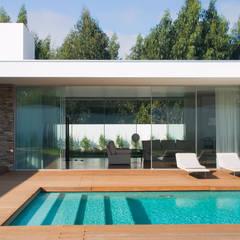 Vista da piscina para a sala: Piscinas  por A.As, Arquitectos Associados, Lda