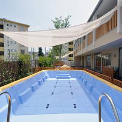 夏場は園庭に組立て式プールを設置: モリモトアトリエ / morimoto atelierが手掛けた学校です。