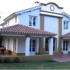 Fachada y jardín delantero:  Houses by Radrizzani Rioja Arquitectos