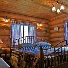 丸太を活かした寝室: Cottage Style / コテージスタイルが手掛けた寝室です。