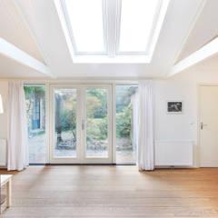 Het zonlicht valt zo naar binnen en is af te schermen.:  Woonkamer door Architectenbureau Vroom