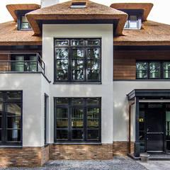 LANDELIJKE RIETGEDEKTE VILLA NAARDEN:  Huizen door DENOLDERVLEUGELS Architects & Associates