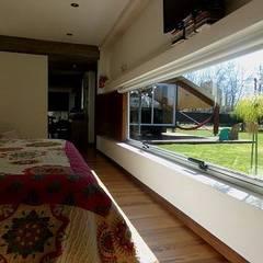 Casa de madera en VILLA ELISA - La Plata: Dormitorios de estilo rústico por juan olea arquitecto