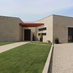 Relação do alçado de entrada principal com o jardim.: Casas  por Sérgio Bouça