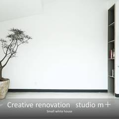 小さな白い家: studio m+ by masato fujiiが手掛けた壁です。,