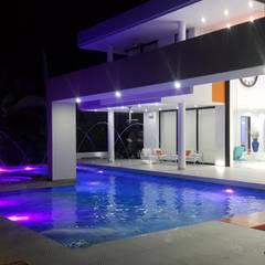 Vista nocturna area de piscina.: Piscinas de estilo  por Camilo Pulido Arquitectos