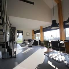 Woonkamer met vide boven de eetkamer: minimalistische Woonkamer door STUDIO = architectuur
