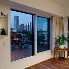 テラスから新宿の夕景: 向山建築設計事務所が手掛けたベランダです。