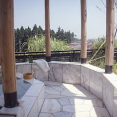 囲炉裏テーブルと露天風呂のある別荘: (株)独楽蔵 KOMAGURAが手掛けたサンルームです。