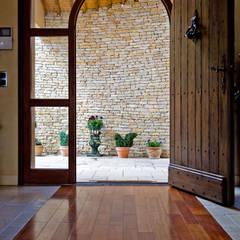 Maison avec couloir vitré et mobilier bois: Portes en bois de style  par Pierre Bernard Création